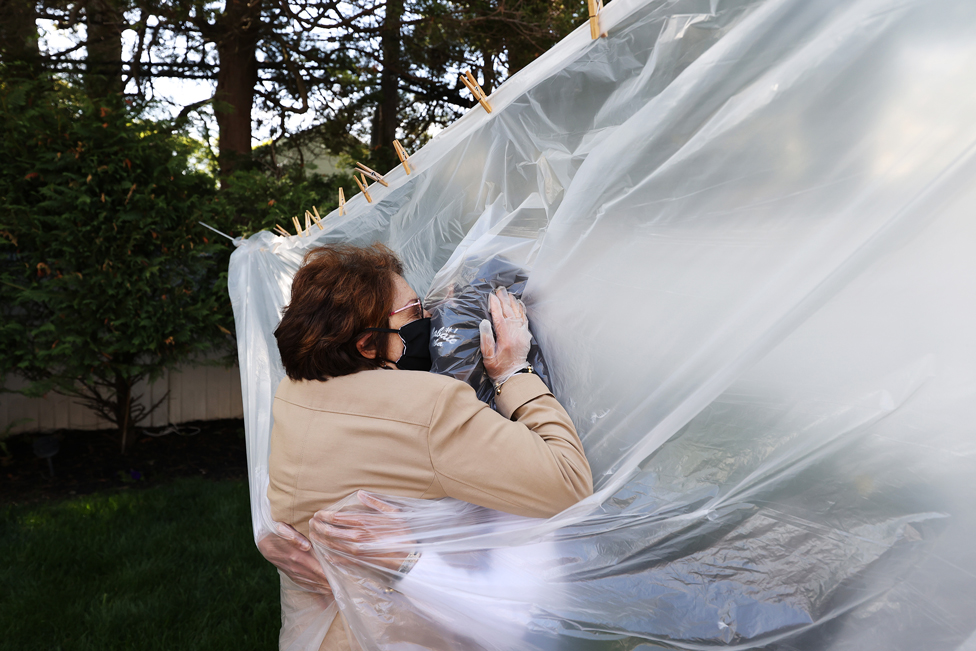 A mother and daughter embrace through a plastic sheet in Wantagh, New York, on 24 May 2020