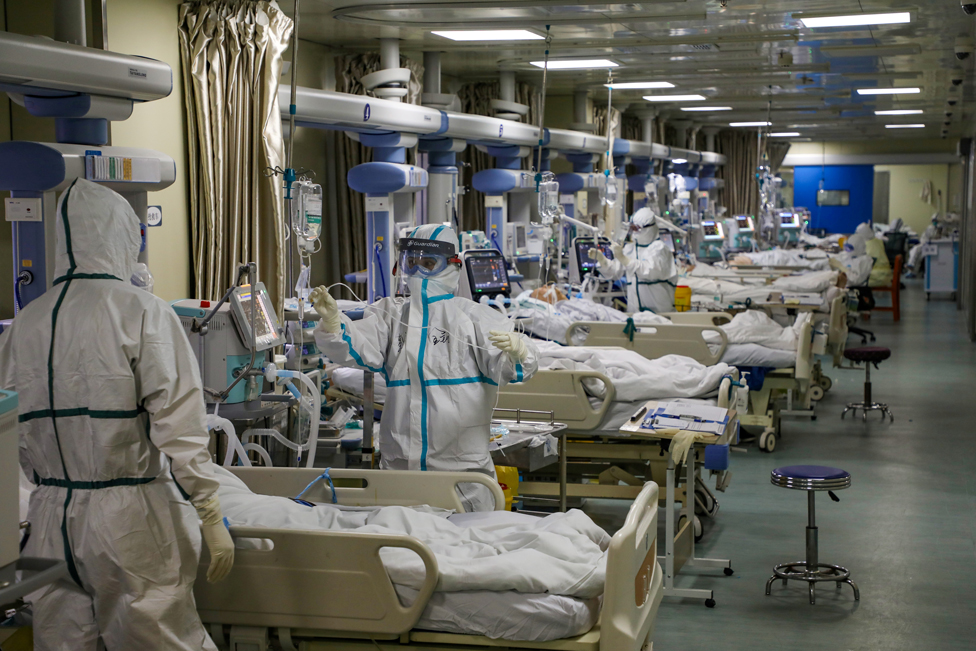 Medical workers in protective suits attend to Covid-19 patients at an intensive care unit in Wuhan, Hubei province, China, 6 February 2020