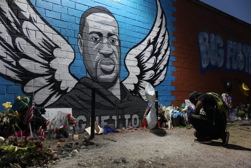 A man kneels in front of a memorial and mural for George Floyd