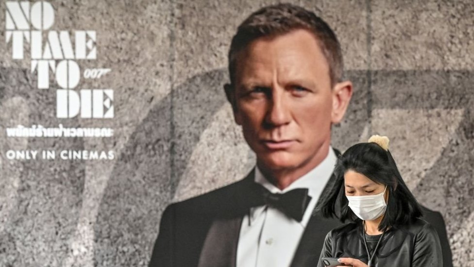 A woman wearing a face mask looks at her phone while standing in front of the new James Bond movie