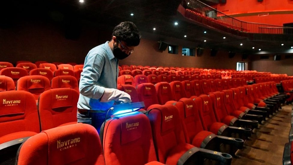 A vendor demonstrates the sterilisation process with an ultraviolet light device on auditorium seats in Bangalore on October 8, 2020