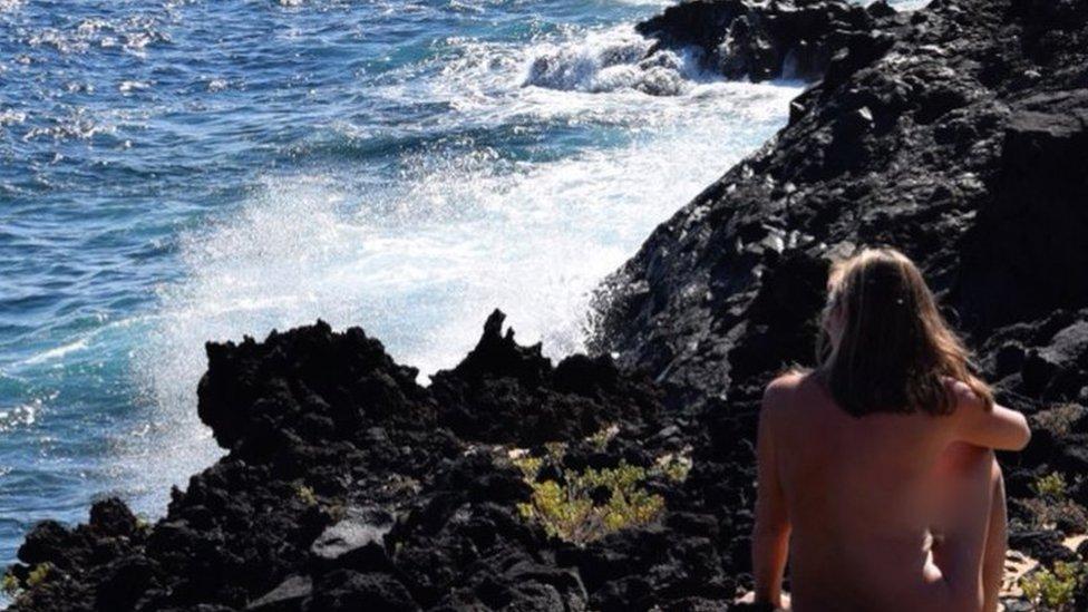 British naturist Donna Price sitting by the sea