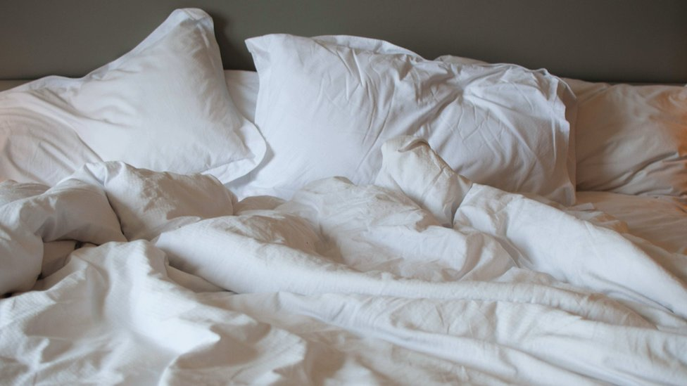 Close-up view of messy bed, with rumpled white linen sheets and big pillows.