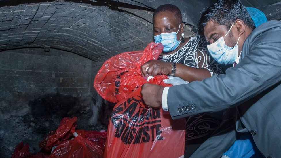 Malawi's Health Minister Khumbize Kandodo Chiponda (C) puts packs of expired Covid-19 Astra Zeneca in a pharmaceutical incinerator to destroy them at Kamuzu Central Hospital in Lilongwe on May 19, 2021.