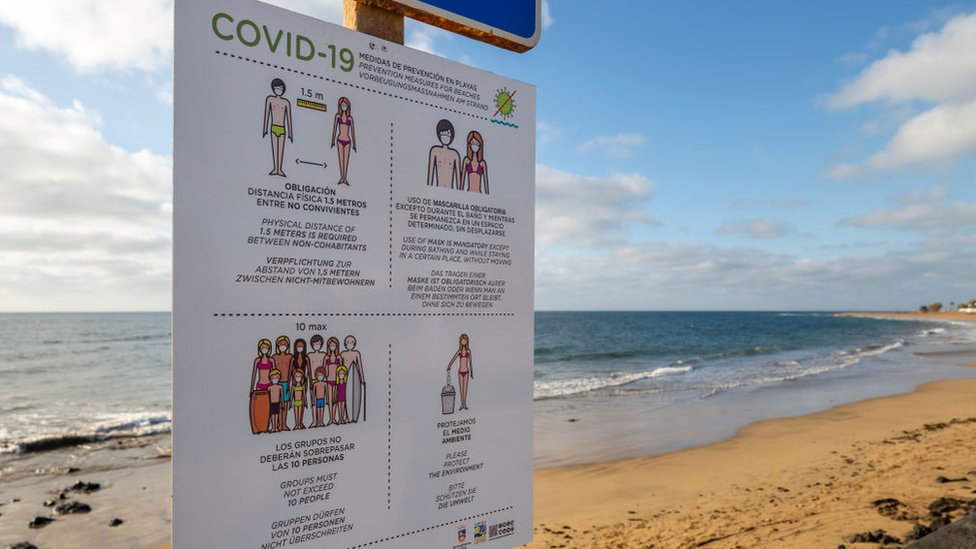 A deserted beach in Lanzarote, Spain, with a billboard showing Covid-19 social distancing rules